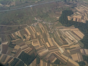 Patchwork strips of agricultural land - it is traditional for families to have some land and if they live in the countryside they will often have a day-job but also keep some chickens, a cow and maybe grow some maize or hay as well.