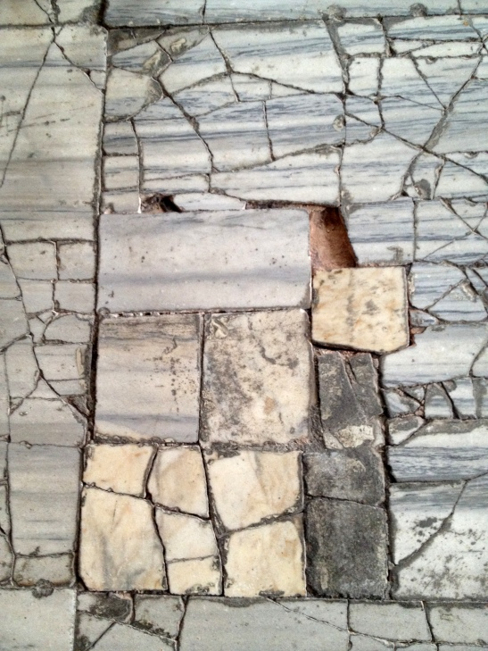 A churchwarden's nightmare - loose tiles, or - in this case - broken marble, on the floor.  They make a tinkling noise when you step on them.