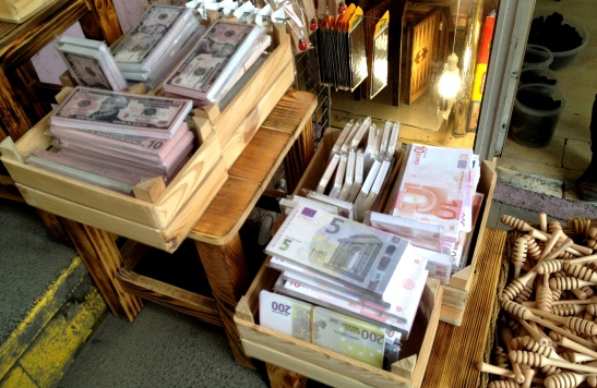 Realistic dollar and euro notes on sale in the market, next to the honey sticks.