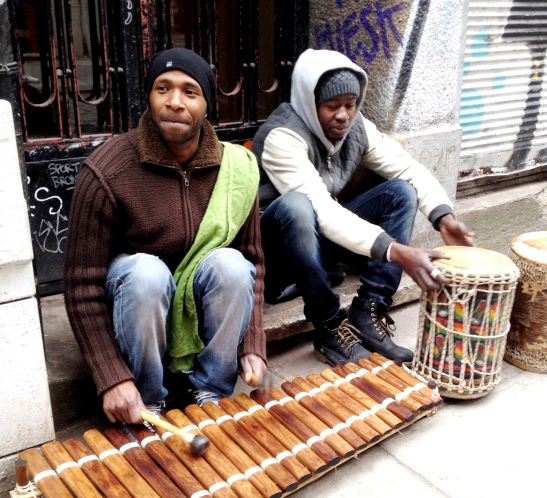 Street musicians - soft singing, balophon & drums.